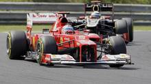 Spain's Scuderia Ferrari driver Fernando Alonso, front, and Finland's Lotus F1 Team driver Kimi Raikkonen, back, compete during the Hungarian Formula One Grand Prix at the Hungaroring circuit outside Budapest, Hungary, Sunday, July 29, 2012. (Darko Vojinovic/AP)