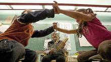 Lukis Jules, 4 years old,left, plays a traditional game with Suli Sotit ,5 years odl as Native Elder Lawrence Michel plays the drum and sings to the pre-school kids at Chief Atahm School in Chase, B.C. on Wednesday November 17, 2010. The Elders are invited to teach the traditional ways to the young students. Aboriginal leaders in B.C. are on the brink of re-inventing education for children on reserves. Now they're fighting for funding. (Jeff Bassett for the Globe and Mail)