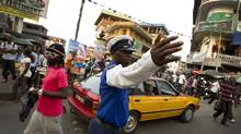 A police officer directs traffic in a bustling downtown intersection in Freetown, Sierra Leone on April 19, 2012. (Peter Power/The Globe and Mail)