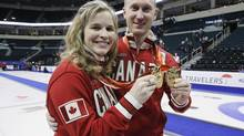 Canadian men and women's curling team skips Jennifer Jones and Brad Jacobs hold their medals at the 2013 Roar of the Rings Canadian Olympic Curling Trials in Winnipeg, Sunday, December 8, 2013. (John Woods/THE CANADIAN PRESS)