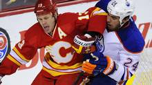 Calgary Flames' Olli Jokinen (L) tries to get away from Edmonton Oilers' Theo Peckham during the first period of their NHL hockey game in Calgary, Alberta, December 10, 2011. The Flames won 3-0. REUTERS/Todd Korol (Todd Korol/Reuters)