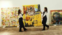 """Sotheby's employees move Jean-Michel Basquiat's Orange Sports Figure. Three of the artist's works set successive auction records this year. The artist's work has been fetching such high prices, past Takashi Murakami's """"open Your Hands Wide, Embrace Happiness!"""" (L) and Cindy Sherman's """"Unititled #421"""" at Sotheby's auction house in London February 1, 2012. The Basquiat is estimated to sell for up to 4 million GBP ($6.3 million) when auctioned on February 15. REUTERS/Luke MacGregor (BRITAIN - Tags: ENTERTAINMENT BUSINESS) (Luke MacGregor/Reuters)"""