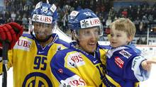 HC Davos' Robbie Earl (R) stand beside as his team mate Peter Sejna holding his son Ownen after winning their final game against Dinamo Riga at the Spengler Cup ice hockey tournament in the Swiss mountain resort of Davos December 31, 2011. REUTERS/Arnd Wiegmann (Arnd Wiegmann/Reuters)