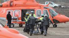 Rescue workers on the scene of a derailed Via train in Burlington, Ont., help an injured passenger onto an ORNGE helicopter on Feb. 26, 2012. (Glenn Lowson For The Globe and Mail/Glenn Lowson For The Globe and Mail)