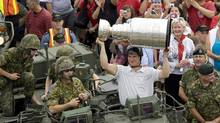 Pittsburgh Penguins captain Sidney Crosby displays the Stanley Cup on an army light armoured vehicle in Halifax on Friday. (ANDREW VAUGHAN/Andrew Vaughan/CP)