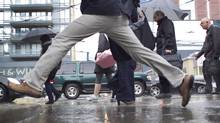 Pedestrians negotiate through the intersection of Spadina and King Street in Toronto on April 26, 2011 as rain continued to fall. (Peter Power/Peter Power/ The Globe and Mail)