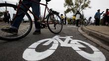 A cyclist walks by a bike lane symbol painted by activists at a memorial on Nov. 14, for pregnant cyclist Jenna Morrison, who was recently killed after being struck by a truck at Sterling and Dundas in Toronto. (Michelle Siu/The Globe and Mail)