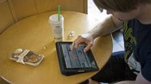 Chip Hanna, 26, explores his newly bought iPad at a Starbucks in Fort Worth, Texas, on Saturday. (Tom Pennington/Getty Images)