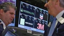 A screen displays the tickers symbols for; Herbalife, Chevron, H&R Block and 3M as traders work on the floor at the New York Stock Exchange, April 25, 2013. (Brendan McDermid/Reuters)