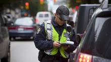 Vancouver police constable Alex Chow pulled over drivers caught on their cell phones in September, 2013. The B.C government, ICBC and the police ran a month-long campaign to discourage distracted driving across the province. (Ben Nelms For The Globe and Mail)