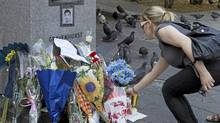 A woman places flowers at a memorial near Concordia University for Lin Jun, a Chinese student who was the victim of a murder and dismemberment, in Montreal June 6, 2012. (CHRISTINNE MUSCHI/REUTERS)