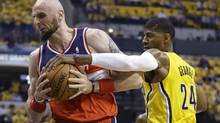 Washington Wizards' Marcin Gortat is defended by Indiana Pacers' Paul George during the first quarter of Game 1 of their Eastern Conference semi-final NBA basketball playoff series in Indianapolis, Monday, May 5, 2014. (Michael Conroy/AP)