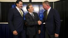 Vancouver Canucks new head coach John Tortorella, centre, shakes hands with Canucks General Manager Mike Gillis, right, next to Canucks owner Francesco Aquilini, left, during a news conference in Vancouver on June 25. (BEN NELMS/REUTERS)