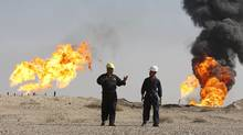 Iraqi workers walk in South Rumaila oil field, in southern Iraq, December 2, 2009. (ATEF HASSAN)