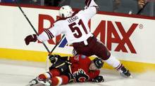 Phoenix Coyotes' Lucas Lessio, left, crashes over Calgary Flames' Sven Baertschi, from Switzerland, during first period NHL preseason hockey action in , Alta., Wednesday, Sept. 25, 2013. (Jeff McIntosh/THE CANADIAN PRESS)