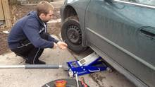 Peter Cheney's son Will learns how to swap wheels at the end of a driving season. (Peter Cheney/The Globe and Mail)