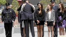 President Barack Obama hugs Diane Wall, wife of Glen James Wall who died at the World Trade Center attack, after laying a wreath at the National Sept. 11 Memorial at Ground Zero in New York, May 5, 2011. (Charles Dharapak/AP/Charles Dharapak/AP)