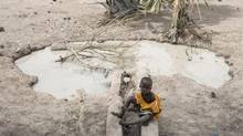 """A boy sits beside a fetid pool of water in Aweil, South Sudan, in early March. A leaked UN report says spreading famine in the region is due to the """"cumulative toll"""" of deliberate government actions. (Mackenzie Knowles-Coursin/AP)"""
