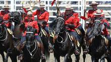 Members of the Royal Canadian Mounted Police musical ride demonstrate their charge before the start of the Calgary Stampede rodeo in Calgary on July 12, 2014. (Todd Korol For The Globe and Mail)