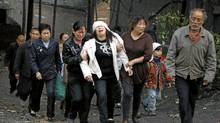 Relatives of a miner killed in an explosion in Yuzhou, China, grieve for their loss on Sunday. (Ken Teh/Associated Press)