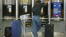 A traveller talks on a payphone at Pearson International Airport in this file photo. (KEVIN FRAYER/CP)