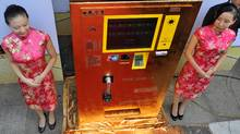 This photo taken on September 23, 2011 shows Chinese bank staff standing by the country's first gold vending machine in the popular Wangfujing Street in Beijing, where shoppers can insert cash or use a bankcard to withdraw gold bars or coins of various weights based on market prices, while each withdrawal is capped at 2.5 kg or one million yuan (about $156,500 U.S.) worth of gold. (STR/AFP/GETTY IMAGES)