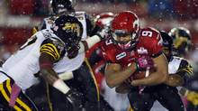 Hamilton Tiger-Cats' Ricardo Colclough, left, closes in on Calgary Stampeders' Jon Cornish during second half CFL football action in Calgary, Alta., Saturday, Oct. 20, 2012. The Tiger-Cats will need to stop the Stamps' run game if they want to defeat the West-leading Stampeders. (Jeff McIntosh/THE CANADIAN PRESS)