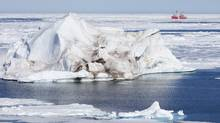 A iceberg floating in Baffin Bay dwarfs the Canadian Coast Guard icebreaker Louis S. St-Laurent in a file photo. Scientists say the bay is being transformed by melting sea ice and glaciers. (JONATHAN HAYWARD/THE CANADIAN PRESS)