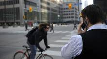 FILE PHOTO. A man on his Blackberry smartphone at the corner of Bay St. and King St. West on February 28 2012. (Fred Lum/The Globe and Mail) (Fred Lum/Fred Lum/The Globe and Mail)
