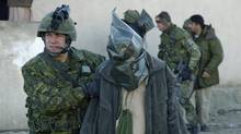 Canadian soldiers lead detainees from a residential compound in Kabul after a raid in 2003. (MCpl Brian Walsh/Department of National Defence)