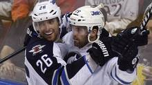 WinnipegJets' Blake Wheeler (26) and Andrew Ladd celebrate after Ladd scored in the third period of an NHL hockey game against the Florida Panthers in Sunrise, Fla., Tuesday, April 3, 2012. (Associated Press)