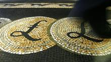 An employee is seen walking over a mosaic of pound sterling symbols set in the floor of the front hall of the Bank of England, in London in this March 25, 2008 file photograph. (Luke MacGregor/REUTERS/Luke MacGregor/REUTERS)