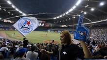 A vendor walks in the crowd during Toronto Blue Jay's preseason baseball game against the New York Mets at Olympic Stadium in Montreal (Christinne Muschi/The Globe and Mail)