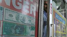 A man exits the doorway of a currency exchange store in New Delhi, India, on Thursday, Nov. 24, 2016. (Anindito Mukherjee/Bloomberg)
