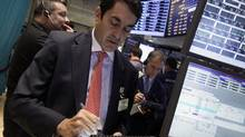 Trader Mark Muller, center, works on the floor of the New York Stock Exchange Wednesday, Oct. 3, 2012. Stocks are mostly higher in early trading on Wall Street Wednesday after a measure of private sector hiring came in better than economists were expecting. (Richard Drew/The Associated Press)