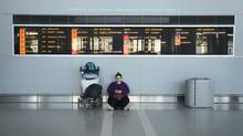 A traveller sits under a flight notice board at Toronto Pearson International Airport on Jan. 8, 2013. (Fred Lum/The Globe and Mail)