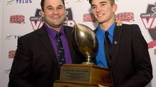 Bishop's University Gaitors' Jordan Heather, right, holds the Hec Crighton Trophy as CIS football player of the year with his coach, Coach of the Year, Kevin Mackey during Vanier Cup celebrations Thursday, November 21, 2013 in Quebec City. (JACQUES BOISSINOT/THE CANADIAN PRESS)