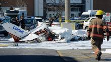 A firefighter and police officers look at the wreckage from a plane crash in a parking lot in Saint-Bruno, Que., on March 17, 2017. (Ryan Remiorz/THE CANADIAN PRESS)