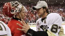 Pittsburgh captain Sidney Crosby shakes hands with Detroit Red Wings goalie Chris Osgood after the Penguins won the Stanley Cup. (Paul Sancya)