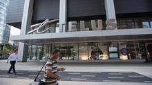 People walk by a Telus store in downtown Toronto. (Gloria Nieto/The Globe and Mail)
