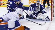 Toronto Maple Leafs goalie Jonathan Bernier makes a save with teammate Carl Gunnarsson, centre, against New York Islanders' Josh Bailey, left, during third period NHL action in Toronto, Tuesday November 19, 2013. (Mark Blinch/THE CANADIAN PRESS)