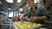 Eric Chong, is seen at Canoe preparing Dim Sum Siu Mai (Dungeness crab and shrimp) and Char Siu Bao (pork buns). (Kevin Van Paassen For The Globe and Mail)