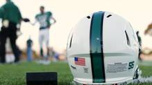 A football helmet's health warning sticker is pictured between a U.S. flag and the number 55, in memory of former student and NFL player Junior Seau, as the Oceanside Pirates high school football team prepares for their Friday night game in Oceanside, California September 14, 2012. (© Mike Blake / Reuters/REUTERS)