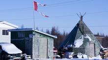 "The remains of a Canadian flag can be seen flying over a building in Attawapiskat, Ont., on November 29, 2011. The Federal Court says it was ""unreasonable"" for the federal government to appoint a third-party manager for the financially troubled First Nations community of Attiwapiskat. (Adrian Wyld/THE CANADIAN PRESS)"
