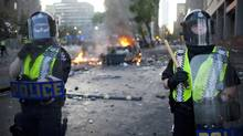Riot police stand guard at Hamilton Street and Georgia Street after the Bruins won the Stanley Cup and cars were set ablaze in Vancouver on June 15, 2011. (Rafal Gerszak/Rafal Gerszak for the Globe and)