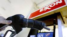 A customer holds a gas pump handle at an Exxon station in Vancouver, Wash. (Don Ryan/Don Ryan/AP)