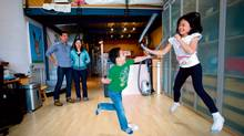 Kirk and Elaine Jong watch as children Kyle and Kali romp in their compact Vancouver loft. It's 'kind of like living in a hotel room,' says Kirk. (DARRYL DYCK FOR THE GLOBE AND MAIL)