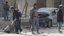 Afghan policemen inspect the site of a motorcycle bomb in the city of Kandahar on Dec. 6, 2011. (JANGIR/AFP/Getty Images)