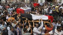 Egyptian relatives and colleagues of policemen who were killed during Wednesday's clashes carry coffins covered with national flags during a military funeral in Cairo on Aug. 15, 2013. Egyptian authorities on Thursday raised the death toll from clashes the previous day between police and supporters of the ousted Islamist president, saying hundreds of people died and laying bare the extent of the violence that swept much of the country and prompted the government to declare a nationwide state of emergency and a nighttime curfew. (Amr Nabil/AP)