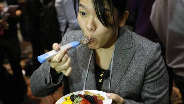 A Japanese reporter with TV Asahi tries out the HAPIfork, a fork that keeps track of the number of fork servings you take, measures how fast you are eating and alerts the user with lights and vibration if you are eating too fast. (RICK WILKING/REUTERS)